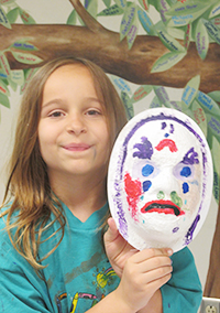 Young girl holding a painted mask